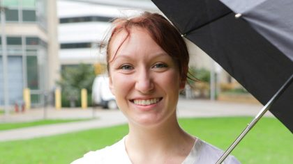 Person with red hair in bun stands outside with umbrella.