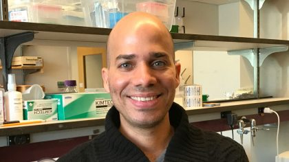 Person with shaved head in front of lab bench