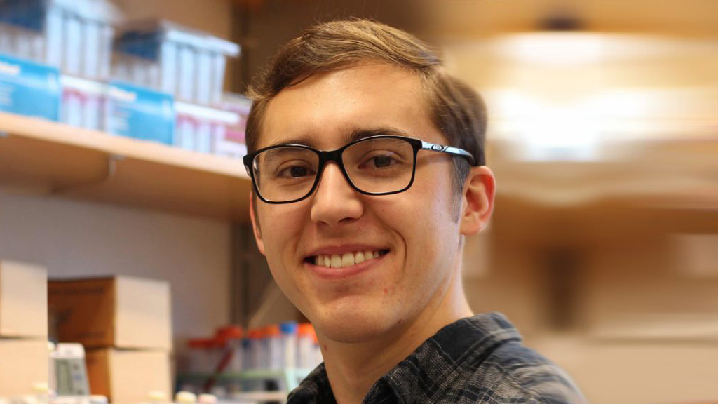 Person with glasses and brown hair in front of lab shelves