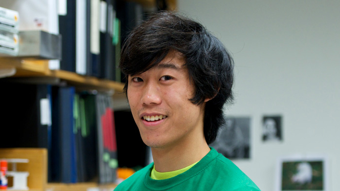 Person with black hair and green sweatshirt in front of lab bench