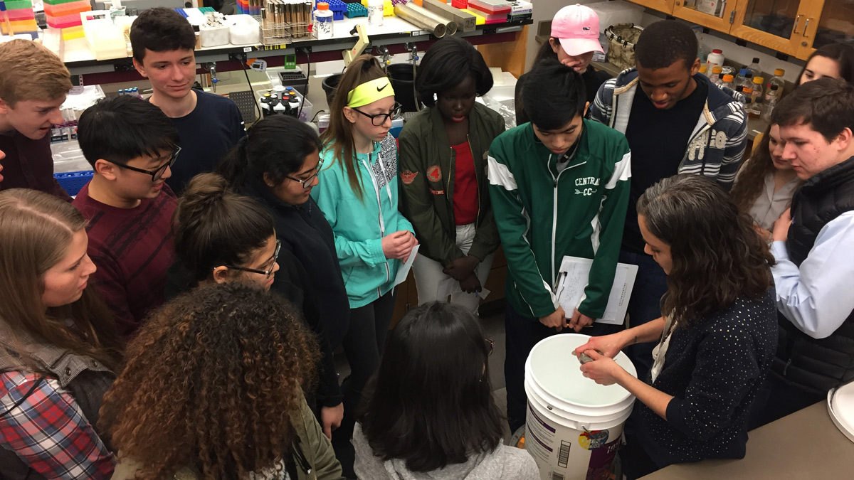Group of students surrounding an instructor, whose hands are over a white bucket