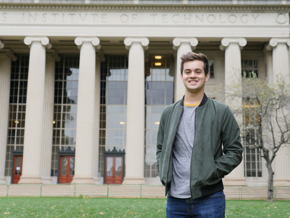Person with short brown hair and green jacket stands in front of MIT pillars.