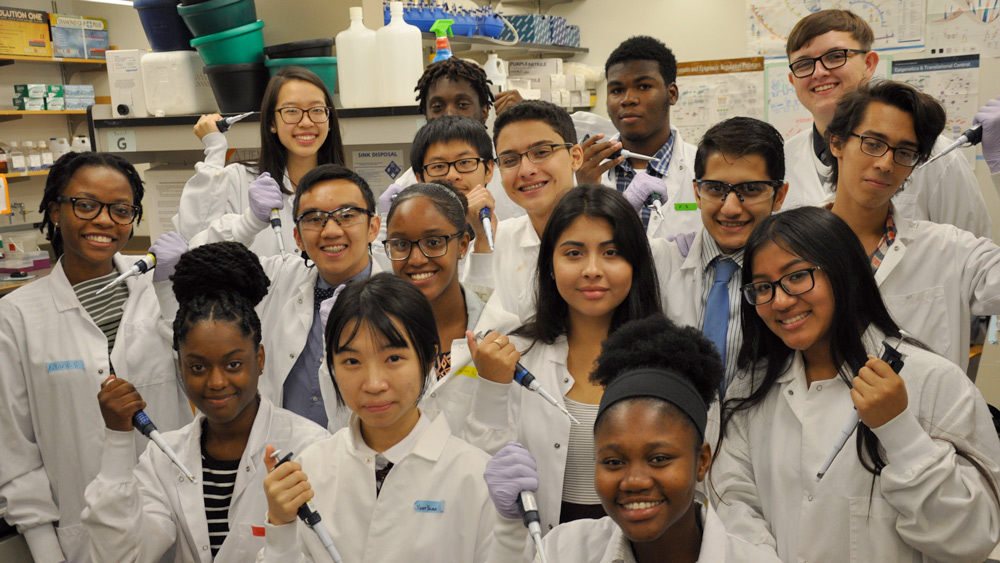 Group of happy female and male students in lab coats holding lab equipment
