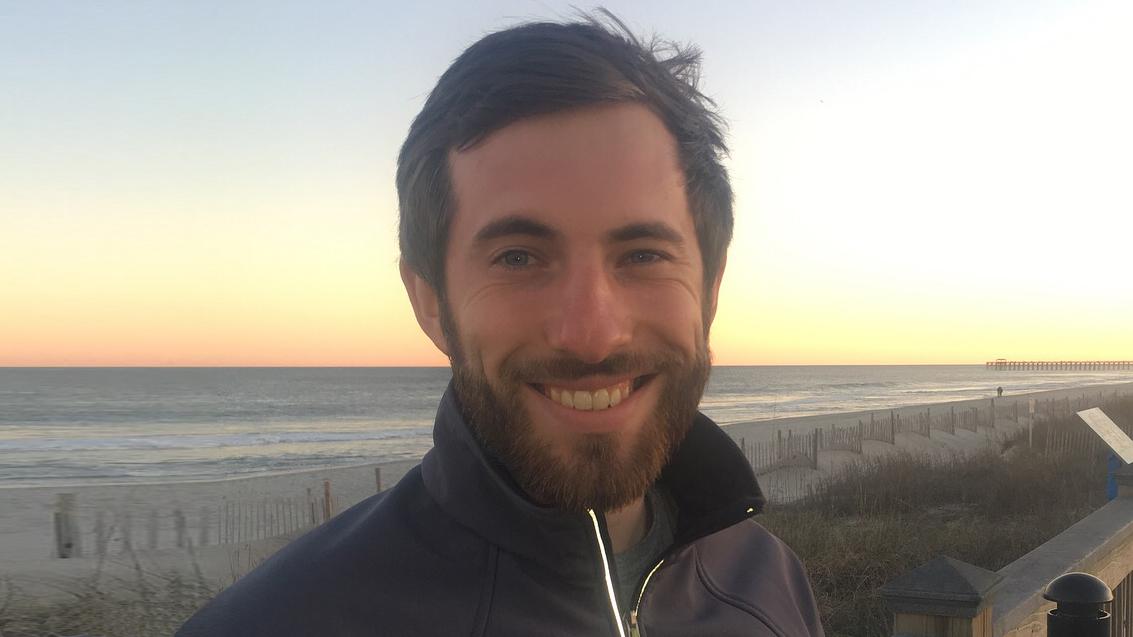 Person with dark hair and beard on sea coast.
