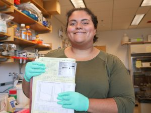 Person smiling with lab notebook