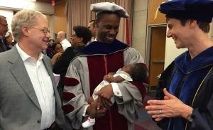 Student at graduation with baby