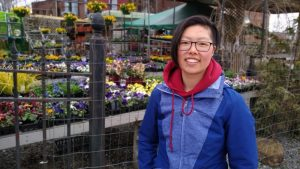 Person smiling by flowers