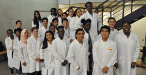 Students in white coats smiling