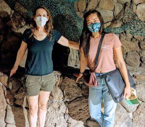 Two women standing by rock wall