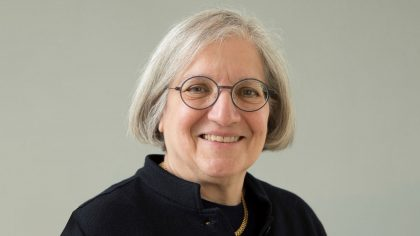 Woman with grey hair and glasses smiling